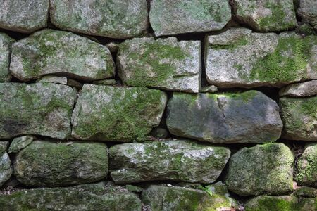 Huge stones, rough surface. Ancient masonry. The rock is covered with green moss. 版權商用圖片