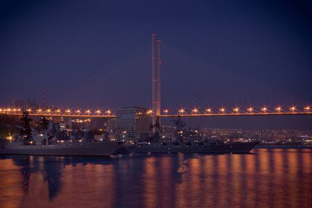 Navy ships in the harbor. Bridge over the bay, night illumination. Far away the city lights. Blue sky, evening, night. Seaport of Vladivostok. Vignetting.