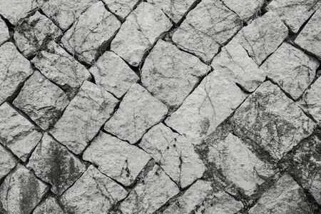 Natural raw stone, diagonal masonry. Ancient fortress wall, foundation. Grunge style. In black and white. 版權商用圖片