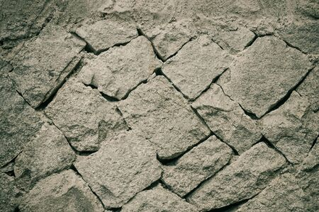 Gray texture, rough rough stone. Ancient masonry, foundation. Grunge style, vignetting.