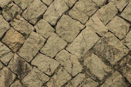 Rough gray stones laid diagonally, natural texture. Ancient building, fortress. Toning.