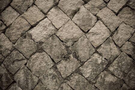 Gloomy cold texture, natural raw stone. Gray rock, diagonal masonry. Vignetting.