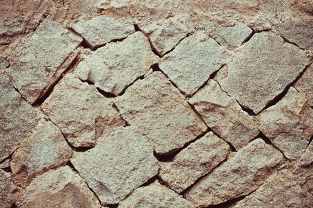 Large untreated stones are laid diagonally. Antique masonry, natural texture. Toning.