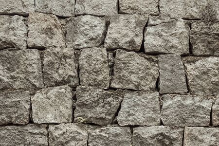 Antique masonry, natural stone, gray tones. Rough, uneven rock is staggered. The fortress wall.