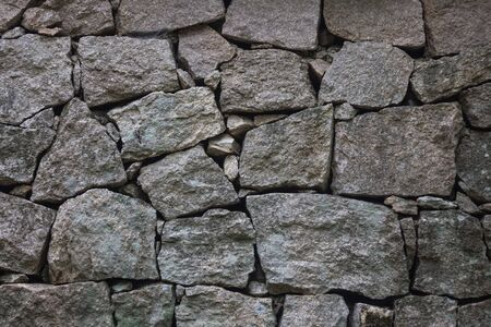 Rough, uncouth stones, rock. Ancient wall, foundation. Cold, gloomy texture. Grey colour.