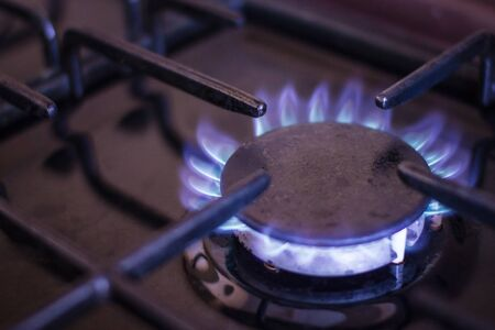 Gas burner with blue flame. Extraction and use of natural gas. Dark background, edges blurred. 版權商用圖片