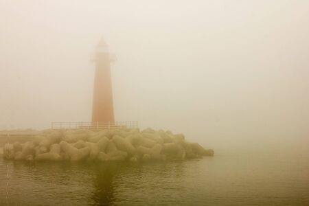 On the seashore a red lighthouse. Everything is in dense fog, poor visibility. Around the dark water. Vintage style.
