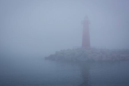 Thick fog, early morning. Unclear outline of the lighthouse. Around the water, the sea. Blue tinting. 版權商用圖片
