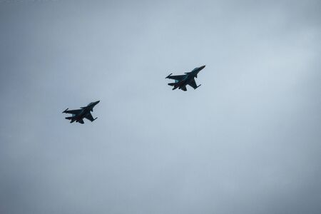 Jet airplanes in gray cloudy sky. Army aviation, modern military industry. Vignetting.