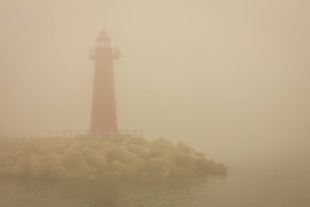 Thick fog on the sea coast. The outlines of the red lighthouse. Around the water. Bad visibility. Vintage toning.
