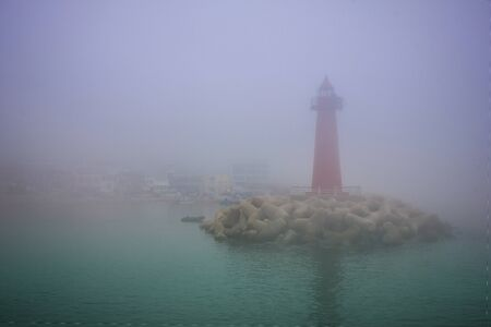 Red lighthouse in the bay. On the shore there are fishing buildings. Everything is in thick fog. Toning. 版權商用圖片