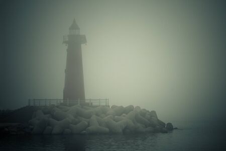 Sea, bay, water all around. Tall lighthouse in the fog. Gray tones, vignetting.