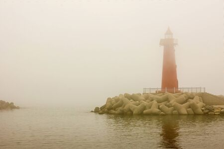 Tall red lighthouse at sea. Misty morning, nothing is visible. Around the dark water. Copy space. 版權商用圖片