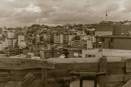 Old wooden balcony, lonely chair. The city, roofs of houses, buildings are visible from above. Cloudy sky Muted tones, vintage toning. 版權商用圖片