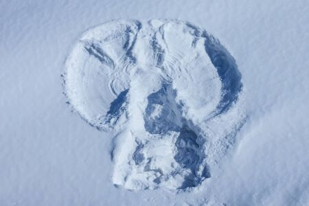 Imprint, outline, the figure of an angel on a snowy surface. Messenger, protector, approaching the holiday. Bright sunlight, top view.