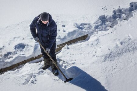 The janitor cleans the yard of the snow. There is a lot of snow around, a thick layer. Cold winter day. Blue toning.