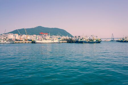 Coastline, ships, bridge. On the shore of the city, modern architecture. View from the water, vignetting. 免版税图像