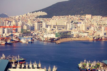 South Korea, Busan panorama. Large international port, many ships. In the distance are tall houses, buildings. The bright blue sea. Solar lighting. Фото со стока