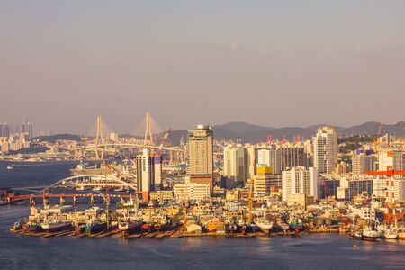 City panorama, Busan seaport. Ships, buildings, bridges, hills. View from the water. Evening lighting, sunset. Фото со стока