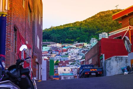 Street, view of the slums. Former fishing village in Busan, small houses, dense buildings on a green hill. In the foreground is a moped, a brick wall of a house. Фото со стока
