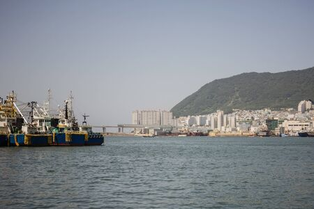 The large seaport of Busan. Fishing ships in the roads. On the shore are tall modern buildings. View from the water. Muted tones, vignetting.