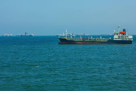 Ships at sea. Freight transportation, shipping. Bright blue water, skyline. Clear sky.