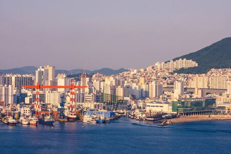 City panorama, high modern buildings on the shore. There are fishing and cargo ships in the harbor. Lateral sunlight. View from above. Фото со стока