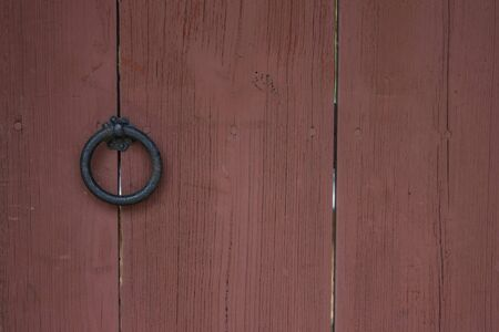 Wooden surface, wide planks. Round iron handle, ring. The entrance is locked, closed. Copy space.