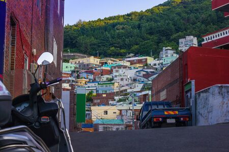 Bucheon, Busan District. Old poor houses on a green mountain, a fishing village. Summer, early evening. View from below.