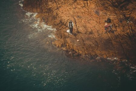 Seascape, dark water, brown stones. Fishermen with fishing rods on a rocky shore. Asia, sunny day. Vintage toning, vignetting.