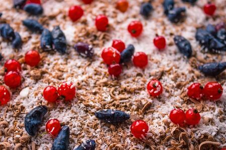 Festive background. Chocolate cake decorated with red and blue berries. Home recipe. The far plan is blurred.