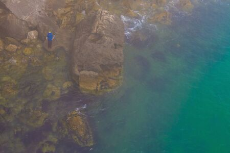 Rocky brown coast, green water. On a rock a man with a fishing rod. View from above. Copy space.