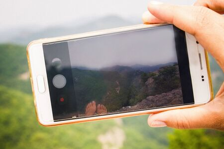 Hand with a smartphone. On the screen is a green landscape, mountains, sky, nature. Vacation, travel. Фото со стока