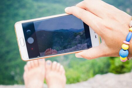 On the phone screen is a mountain landscape and female legs. Girl makes a photo. Freedom, vacation, solo travel.