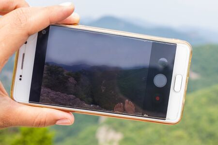 Green landscape on the smartphone screen. Travel photography. In the foreground is a hand with a phone. Mountains, rocks, space. Фото со стока