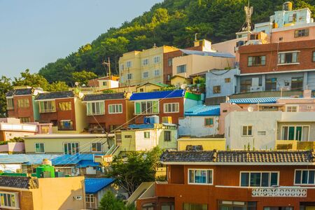 A fishing village on a hillside. Small authentic houses of different colors. Local attraction. Sunny summer day. Фото со стока