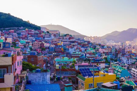 Small houses on a hillside, messy building, rookery. Busan historic district, Korea. Showplace, tourist place. Far mountains, sky. Early summer evening. Фото со стока