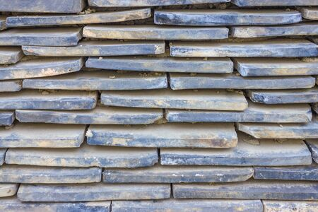 The old tiles are piled in rows. Narrow stripes, staggered. Dirty surface. Фото со стока