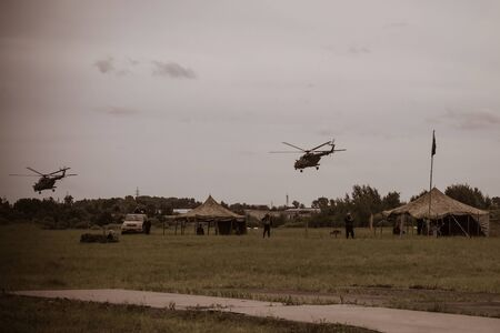 Military camp, base, without identification marks. Men with weapons. Camouflage tents. There are two helicopters in the sky. Muted tones, vignetting.