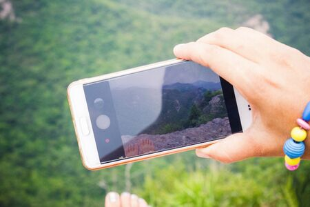 Vacation, summer day in nature. Smartphone in a female hand. A girl takes pictures, shoots a video. On the screen are green mountains, sky.