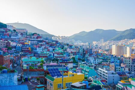 Gamcheon Culture Village, Busan area, tourist attraction. Small colored houses, roofs, messy buildings. Far mountains, sky. Lateral sunlight. Summer.