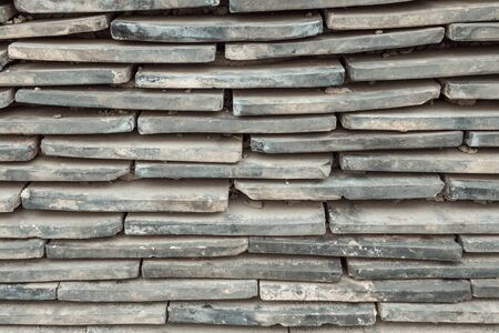 The tile is stacked. Narrow horizontal lines, staggered. Dirty, dusty surface. Gray tones.
