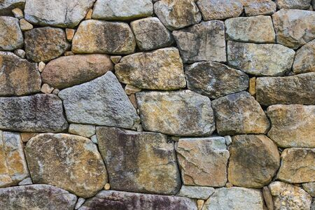 Large cobblestones of various shapes. Rough, untreated stones. Ancient masonry.