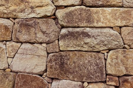 Ancient masonry, large stones. Rough texture. The fortress wall. Brown tinting.