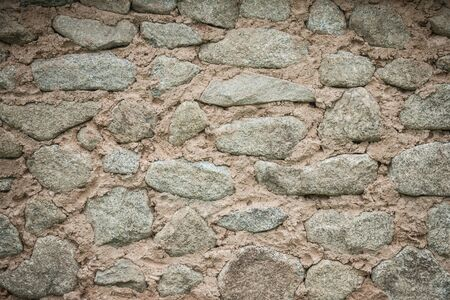 Old fortress wall, foundation. Rough, untreated cobblestones of various shapes. Vignetting. Фото со стока