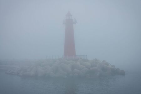 Dense fog at sea, poor visibility. There is a red lighthouse in the bay, dark water is around. Early morning. Vignetting. Фото со стока