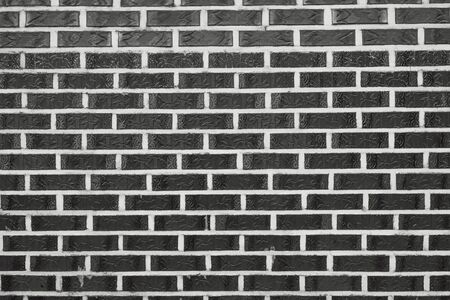 Narrow rectangular tile staggered. White seams, lines. Wall, interior, decor element. In black and white.