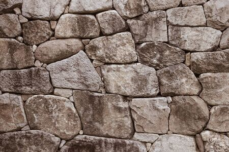 Ancient masonry. Gray fortress wall. Rough, untreated surface. Cold stone. Muted tones, vignetting. Фото со стока