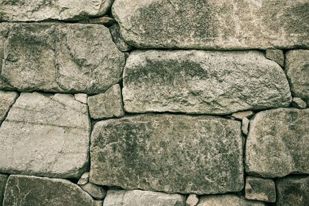 Dungeon, prison, jail. Strong, reliable wall, old masonry. Rough stone, natural texture. Gray tones. Фото со стока