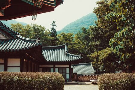 House, manor in the mountains. Traditional korean architecture. Around the green trees. Far mountains, sky. Toning.